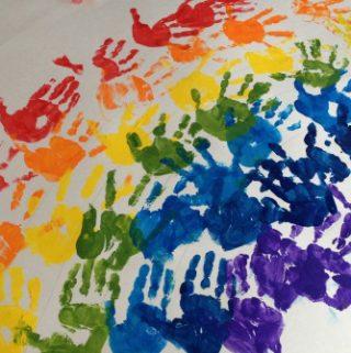 Preschoolers making a Hand Printed Rainbow Art